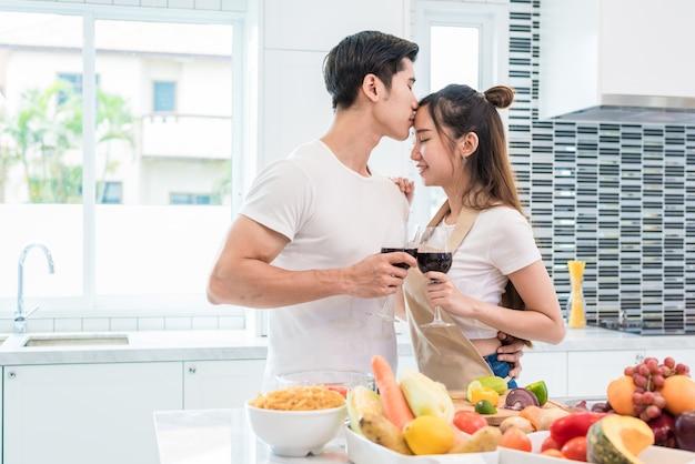 Aziatische minnaars of paren die voorhoofd en het drinken wijn in keukenruimte thuis kussen