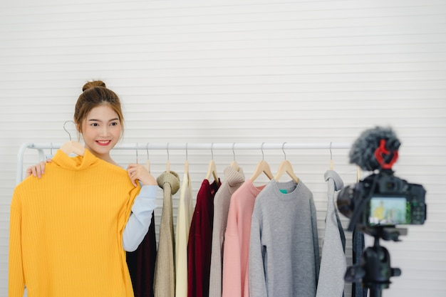 Aziatische mode vrouwelijke blogger online influencer met boodschappentassen en veel kleding