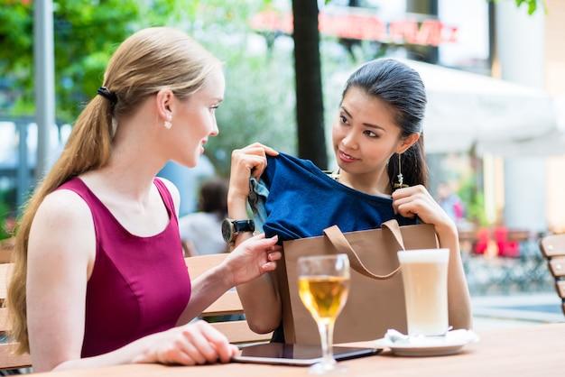 Aziatische modieuze jonge vrouw die aan haar beste vriend een nieuwe trendy aankoop toont