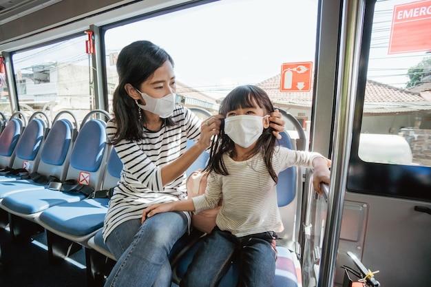 Aziatische moeder brengt haar dochter naar school door met het openbaar vervoer met de bus te reizen en een gezichtsmasker te dragen
