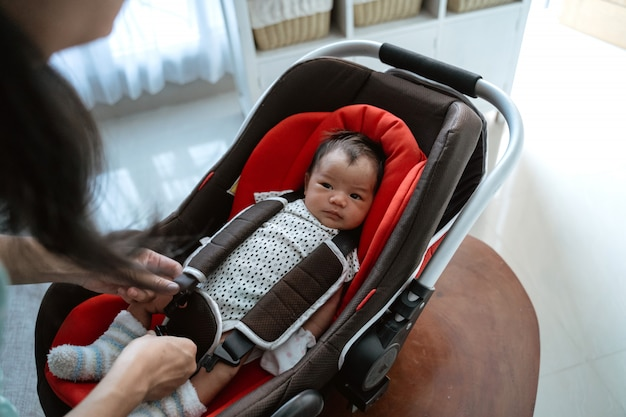 Aziatische moeder die baby zet in zetel