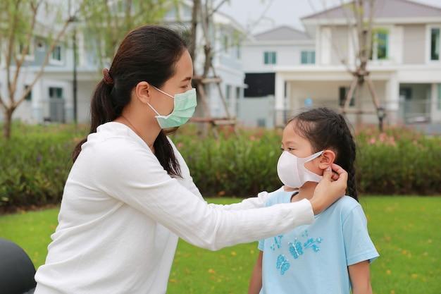Aziatische moeder die beschermende gezichtsmaskers draagt voor haar dochter in de openbare tuin tijdens coronavirus en griepuitbraak
