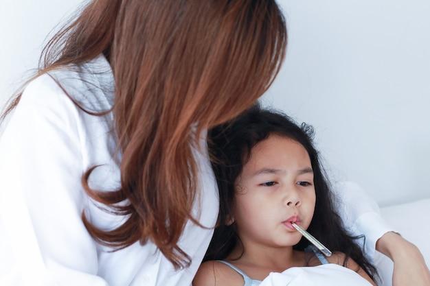 Aziatische moeder die de temperatuur van haar dochter meet. kind is ziek met hoge koorts en heeft het warm in bed.