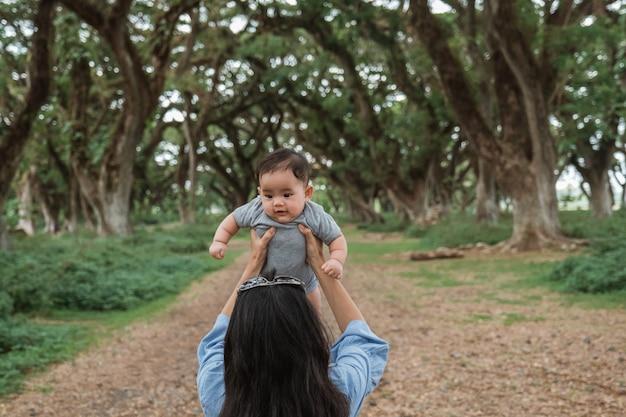 Aziatische moeder die een baby in het park steunt