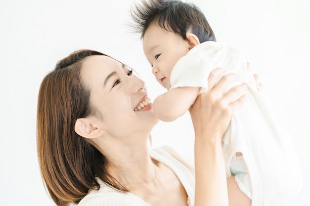 Aziatische moeder die een baby vasthoudt in de lichte kamer