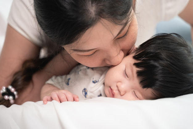 Aziatische moeder die en een baby kust die zacht op bed en liefde slaapt, gelukkig voelt.