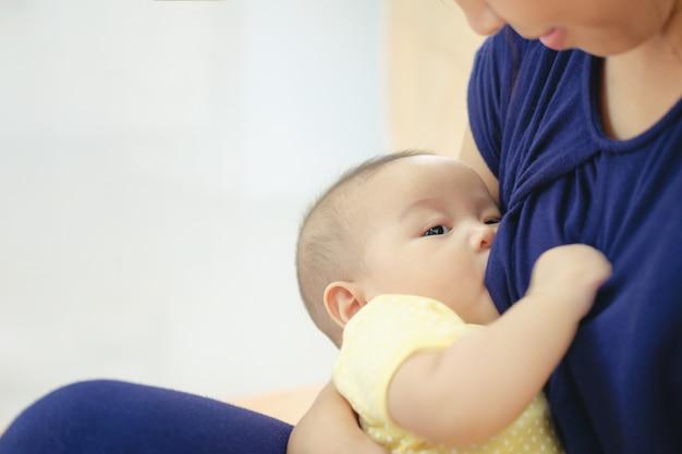 Aziatische moeder die en haar baby de borst geeft geven