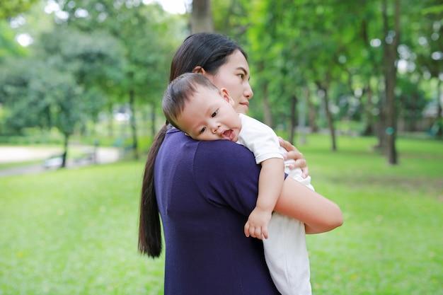 Aziatische moeder die haar baby van de zuigelingsbaby in de de zomertuin draagt.
