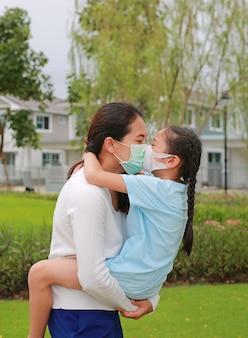 Aziatische moeder die haar dochter draagt met een beschermend gezichtsmasker en zoenen in de openbare tuin tijdens coronavirus en griepuitbraak