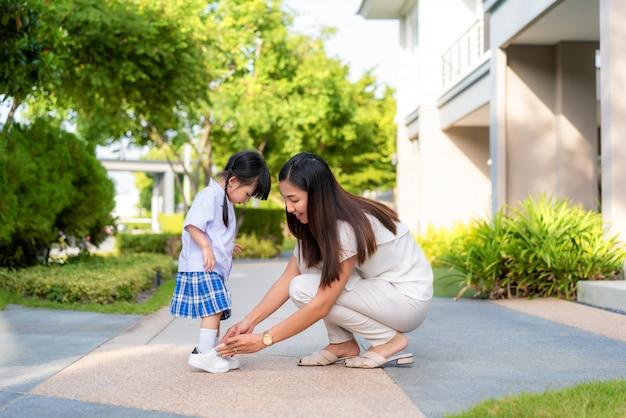 Aziatische moeder die haar dochter helpt zetten schoenen Premium Foto
