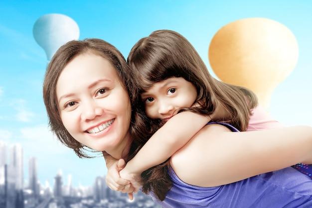 Aziatische moeder die haar kleine meisje op haar rug draagt met kleurrijke luchtballon die met stadsachtergrond vliegt