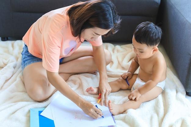 Aziatische moeder die haar schattige babyjongen leert kleurpotloden te gebruiken