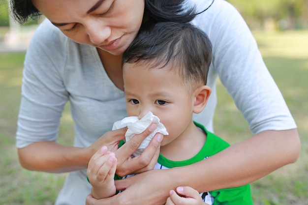 Aziatische moeder die haar zoon helpt om zijn neus met weefsel in de tuin te blazen openlucht.