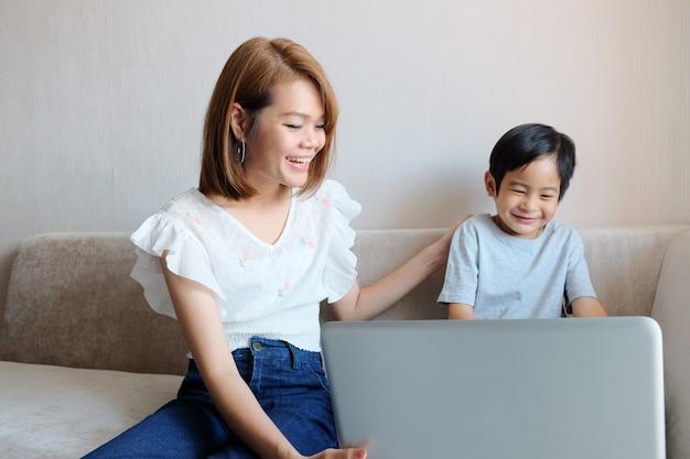 Aziatische moeder die haar zoon voor gebruiklaptop computer onderwijst