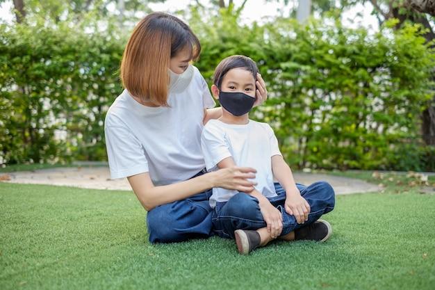 Aziatische moeder draagt een gezichtsmasker aan haar zoonsjongen thuis tuin