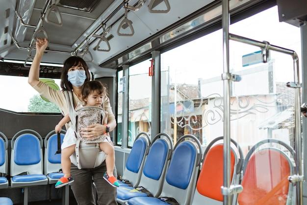 Aziatische moeder draagt een masker en draagt haar kind terwijl ze zich tijdens het reizen aan de bus vasthoudt