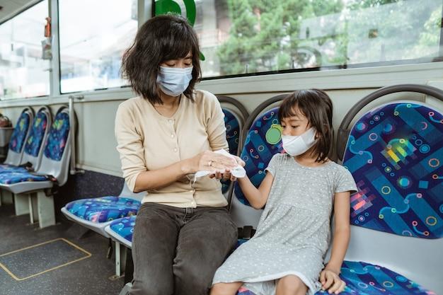 Aziatische moeder draagt een masker met haar dochter terwijl ze een tissue gebruikt om haar handen schoon te maken terwijl ze in de bus zit