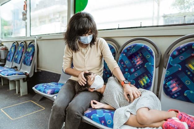 Aziatische moeder draagt een masker samen met een dochter die tijdens een busreis op een bank slaapt