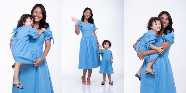 Aziatische moeder en blanke dochter staan en dragen samen dezelfde blauwe blousejurk. klein meisje houdt de hand van de moeder vast en glimlacht met liefde. witte achtergrond geïsoleerd