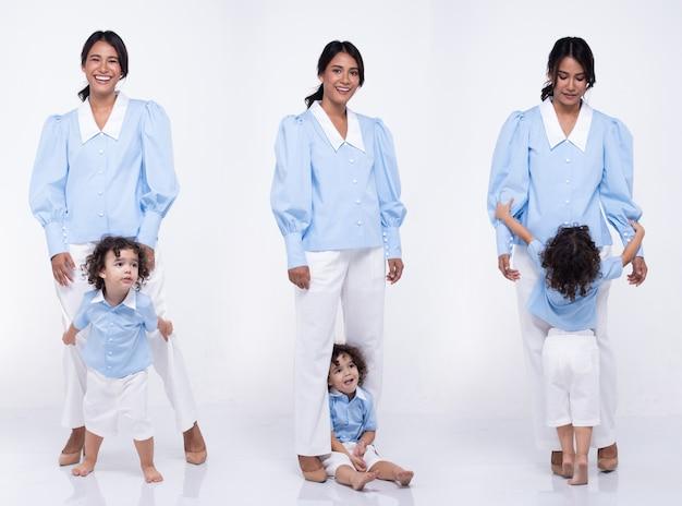 Aziatische moeder en blanke dochter staan en dragen samen dezelfde blauwe broekjurk. klein meisje houdt de hand van de moeder vast en glimlacht met liefde. witte achtergrond geïsoleerd