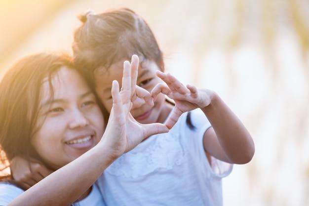 Aziatische moeder en dochter die hartvorm met handen samen met liefde op het gebied maken