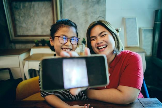 Aziatische moeder en dochter die het slimme telefoonscherm tonen en met gelukgezicht lachen