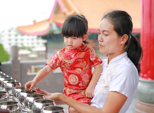 Aziatische moeder en dochter die in traditionele kleding muntstukken in een monnikskom zetten bij chinese tem