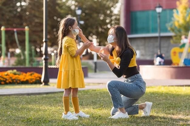 Aziatische moeder en dochter die medische maskers in openlucht dragen