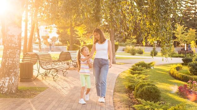 Aziatische moeder en dochter die samen in het park lopen