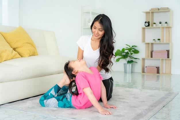 Aziatische moeder en dochter die yogaoefeningen in woonkamer thuis doen