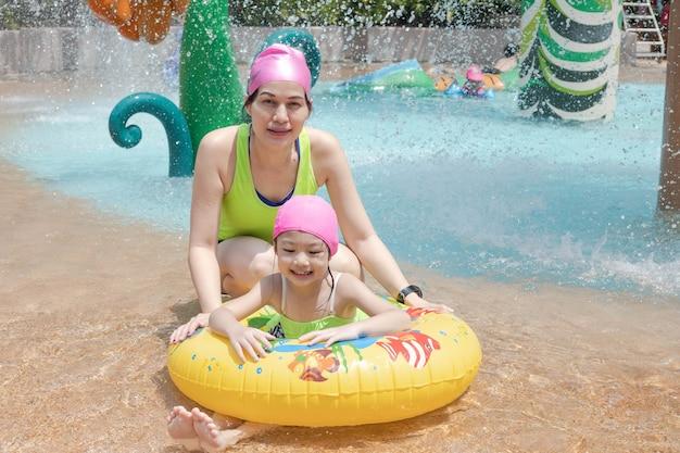 Aziatische moeder en dochter in zwembad, aquapark. zonnige zomer.