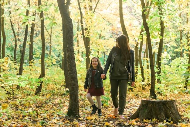 Aziatische moeder en dochter lopen hand in hand in het park, ze dragen warme kleren alleenstaande ouder