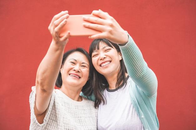 Aziatische moeder en dochter nemen selfie met smartphone voor verhaal app