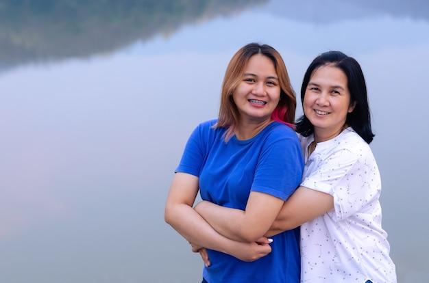 Aziatische moeder en dochter samen knuffelen op meer achtergrond