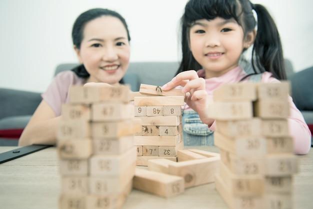 Aziatische moeder en dochter spelen houten blok toren stapelspel in gezellig modern huis