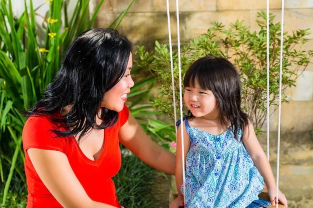Aziatische moeder en dochter thuis in tuin