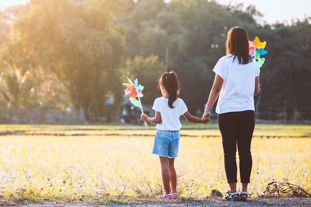 Aziatische moeder en dochterholdingshand en samen het spelen met het stuk speelgoed van de windturbine op het padiegebied