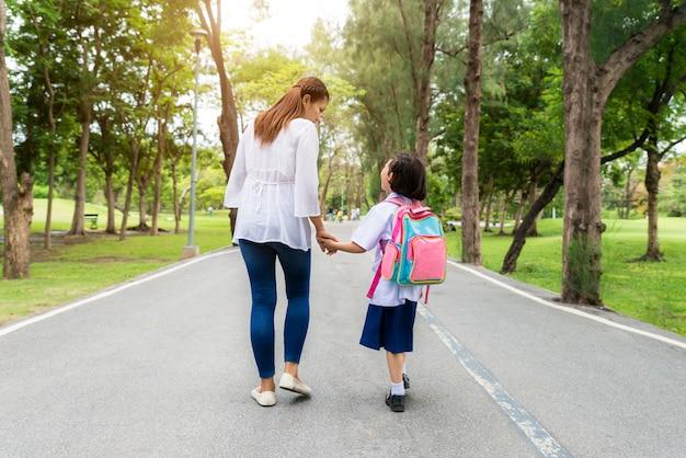 Aziatische moeder en dochterstudent die naar school lopen.