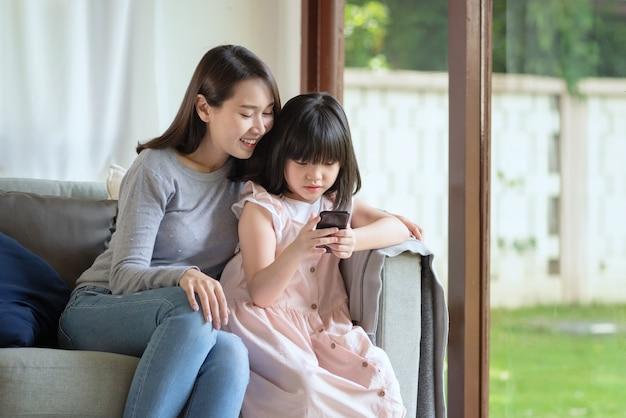 Aziatische moeder en haar dochter gebruiken thuis graag internet via smartphone