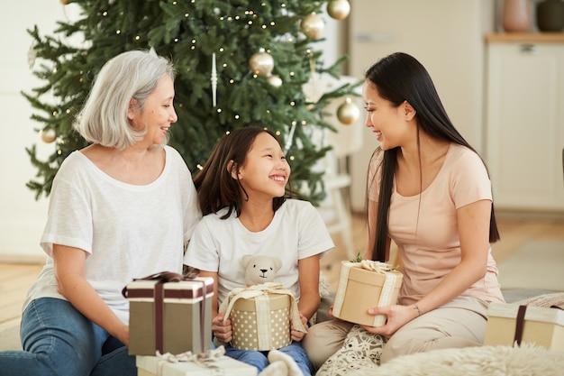Aziatische moeder en haar dochter met kleindochter die elkaar feliciteren met kerstmis en cadeautjes geven zittend op de vloer