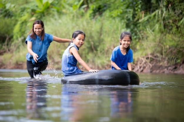 Aziatische moeder en haar dochters die samen in de rivier spelen