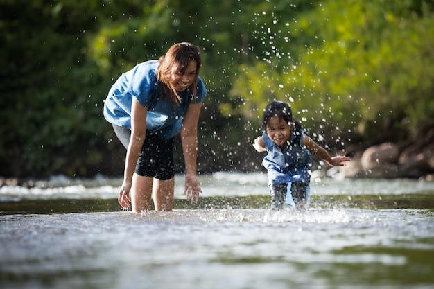 Aziatische moeder en haar kind meisje spelen in de rivier samen met plezier