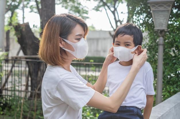 Aziatische moeder en haar zoon dragen van beschermende maskers