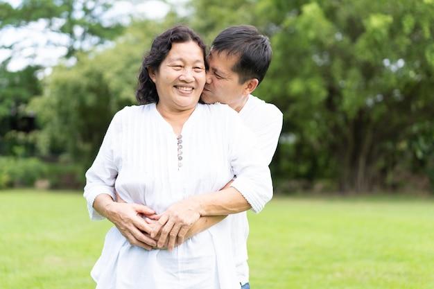 Aziatische moeder en jonge zoon staan en kussen samen in het park