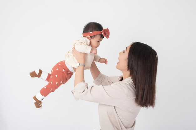 Aziatische moeder en schattig babymeisje zijn gelukkig op witte muur