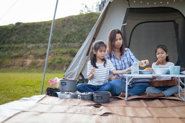 Aziatische moeder en twee kindmeisjes die plezier hebben om buiten de tent te picknicken op de camping in de prachtige natuur.