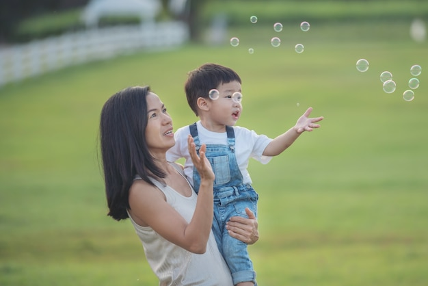 Aziatische moeder en zoon bellen buiten blazen. schattige peuter jongen spelen met zeepbellen op zomer veld. handen omhoog. gelukkig kindertijdconcept. authentiek levensstijlbeeld.