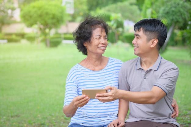Aziatische moeder en zoon van middelbare leeftijd kijken naar elkaar en kijken naar een smartphone met een glimlach en gelukkig zijn in het park is een indrukwekkende warmte