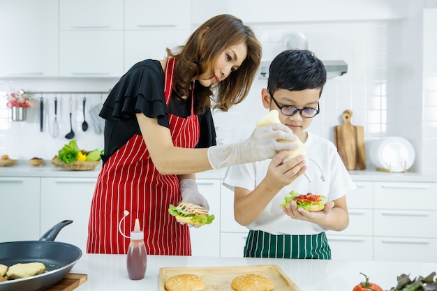 Aziatische moeder en zoon voegen mayo toe aan verse hamburger tijdens het koken van lunch in moderne lunch in de keuken thuis. leren door te doen van modern kid comcept.