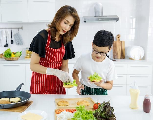 Aziatische moeder en zoon zetten bladeren van verse sla op broodjes terwijl ze thuis hamburgers bereiden voor de lunch. concept voor onderwijs en leren door echt te oefenen in een modern gezin.